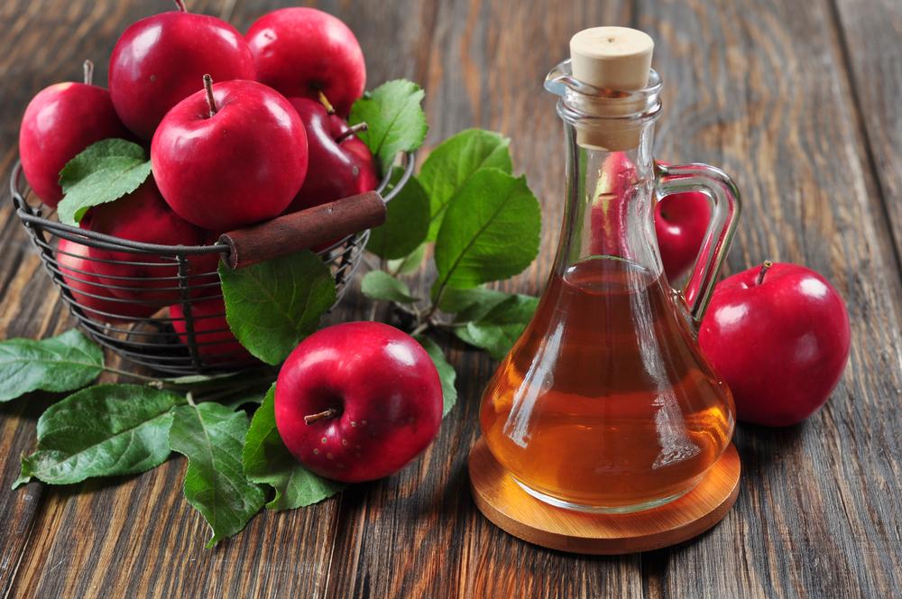 Eine Schale mit Äpfeln neben einem Fläschchen Apfelessig